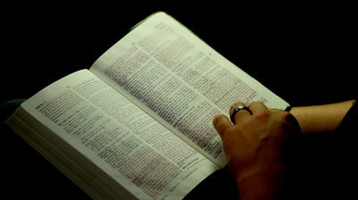 stock-footage-man-reading-bible-with-only-hands-and-bible-showing